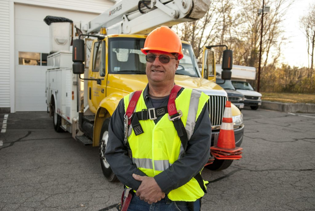 John Lunn standing in front of his boom truck while wearing protective equipment.